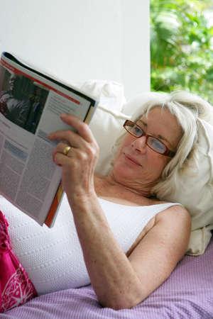 pleasure of reading: Elderly woman reading a magazine