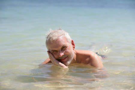Grey-haired man laying in the sea photo