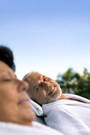 Husband and wife relaxing on sun loungers Stock Photo - 13882643