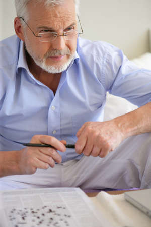 Man completing crossword puzzle photo