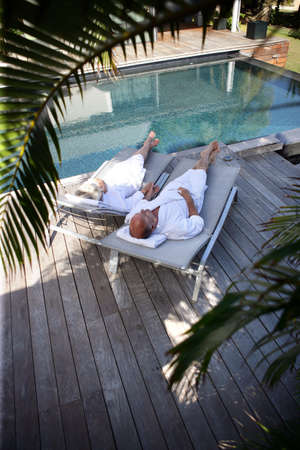 contented: Elderly couple on sunloungers by a pool Stock Photo