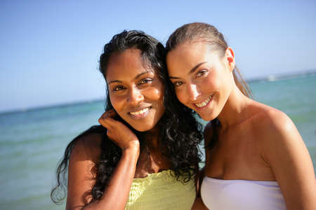 Two attractive female friends stood at the beach Stock Photo - 13883598