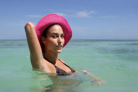Brunette wearing hat and swimming photo
