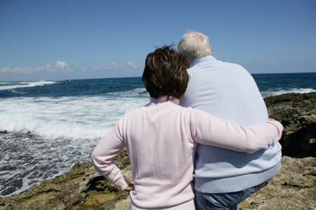 man rear view: Retired couple staring out over the ocean Stock Photo