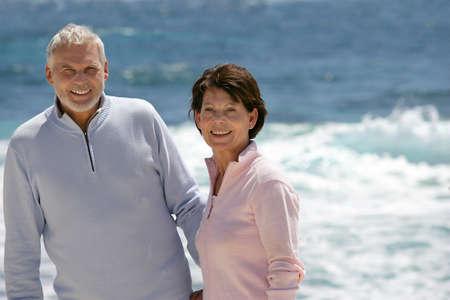 hombres maduros: Pareja de ancianos disfrutando de paseo en la playa