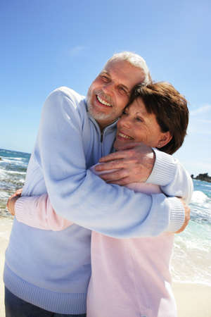 Older couple hugging on a beach photo