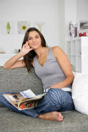 young girl barefoot: Woman sat at home reading magazine on couch Stock Photo