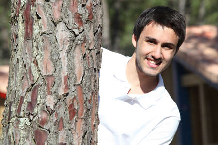 young unshaven: young man behind tree trunk