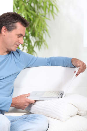 outworking: Man relaxing on sofa with laptop