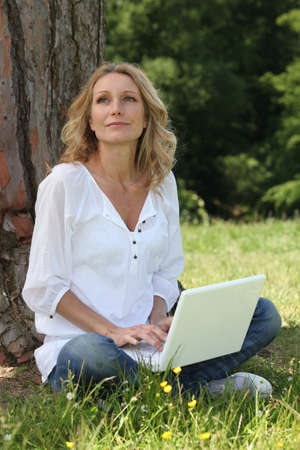 Woman sitting on grass with a computer photo