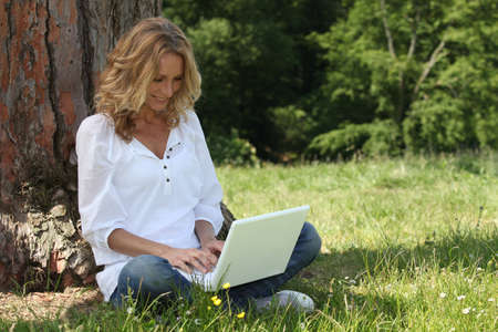 Woman laughing at her laptop computer in the park photo