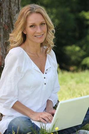 unwinding: Woman on laptop under tree