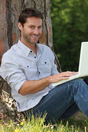 shirtsleeves: Smiling man sitting with laptop computer in the park Stock Photo