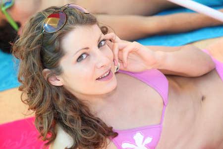 Young girl in a bikini on the phone Stock Photo - 13884371