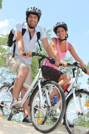 willing: Couple biking on the edge of slope
