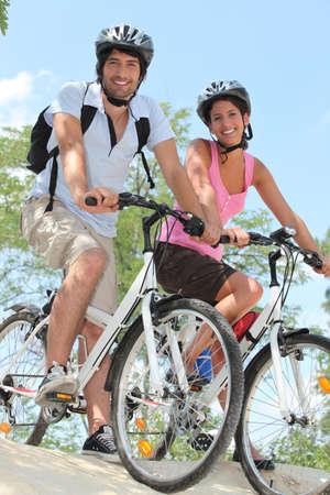 cycling helmet: Couple biking on the edge of slope