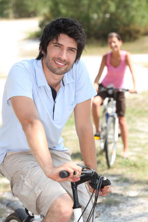 Couple riding bikes in the countryside Stock Photo - 13883775