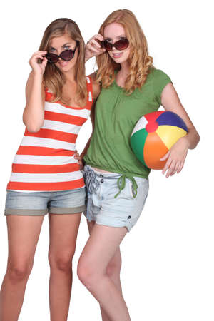 Two attractive girls holding inflatable beach ball photo