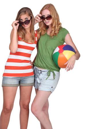 beach ball girl: Two attractive girls holding inflatable beach ball