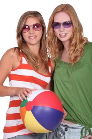 tinted: Studio shot of two girlfriends with a beachball Stock Photo