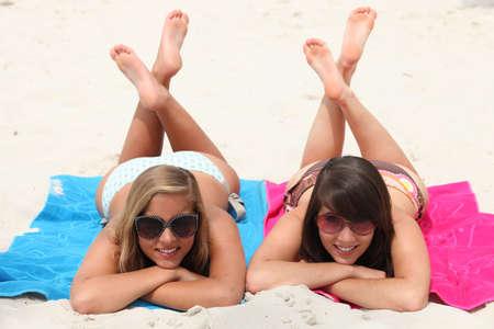 piedi nudi di bambine: Giornata di ozio sulla spiaggia: due ragazze sdraiato sul ventre con le gambe incrociate