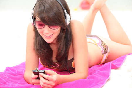 Young woman sunbathing and listening to music on headphones photo