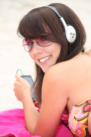 Girl listening to music on the beach photo