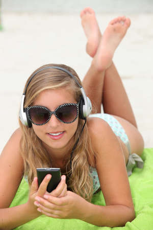 Young woman listening to music while tanning at the beach photo