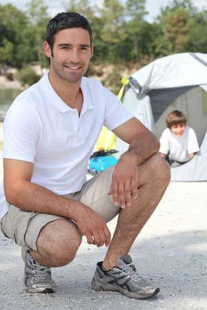 en cuclillas: Padre e hijo de camping