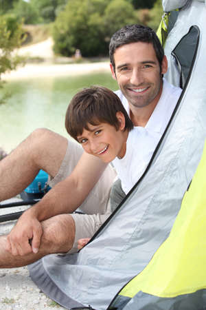 Father and son camping by a lake photo