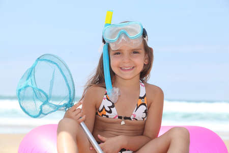 Young girl on the beach with snorkel, mask and fishing net photo