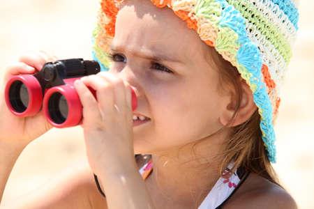 Little girl on the beach with binoculars photo