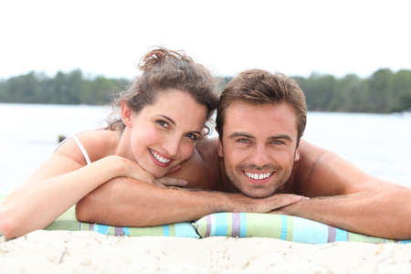 mid adult couple: Couple laying by lake Stock Photo