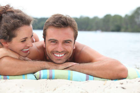 easygoing: Couple relaxing by the lake Stock Photo
