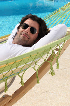long weekend: Man laid in hammock by swimming pool Stock Photo