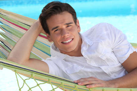 unwind: Man laid in hammock in front of swimming pool Stock Photo