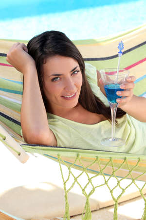 laid back: Woman having a cocktail drink in a hammock