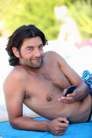 virile: Man in swimsuit looking at his phone