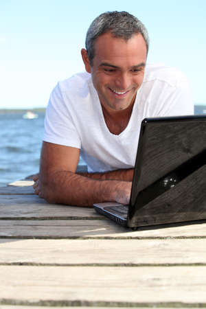 Man using his laptop on jetty photo