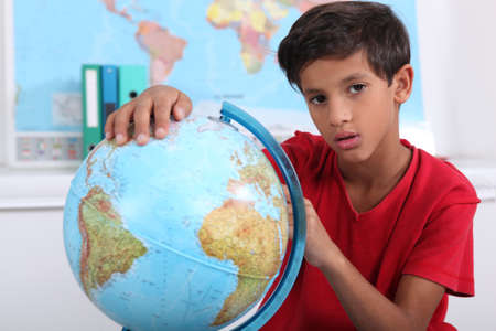 wavering: Pupil with globe Stock Photo