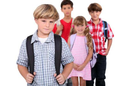 rebellious: Four schoolchildren with backpacks