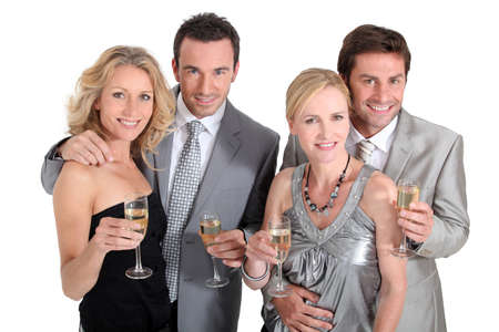 silver dress: Double date: couples in party dress drinking champagne Stock Photo