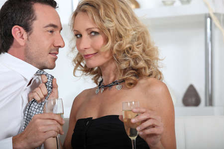 two sexy women: Flirtatious couple drinking champagne at home