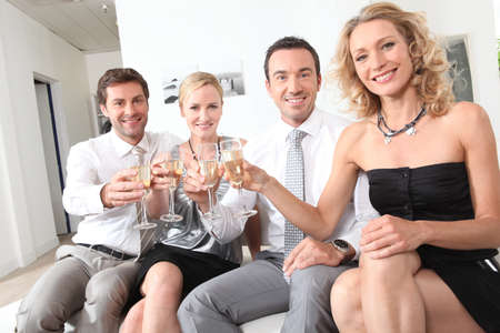 couples sitting holding champagne glasses photo