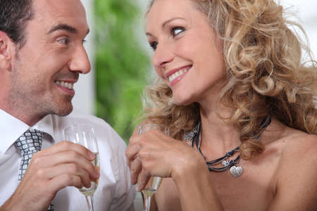 wooing: Closeup of couple drinking champagne and looking into each others eyes