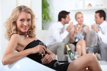 Blond woman sitting holding champagne Stock Photo - 13905877