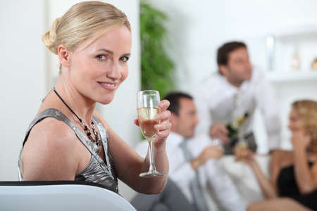 Woman drinking champagne at a party photo