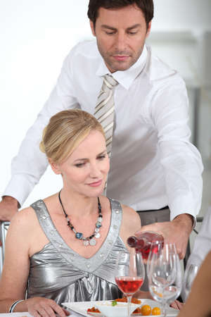 A man serving wine to a woman at the start of a posh dinner. photo
