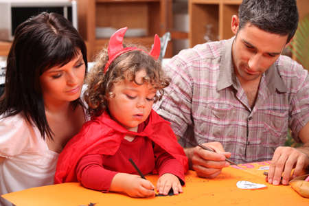 mother and father with child disguised as devil Stock Photo - 13914316