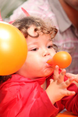 Child blowing up a balloon photo